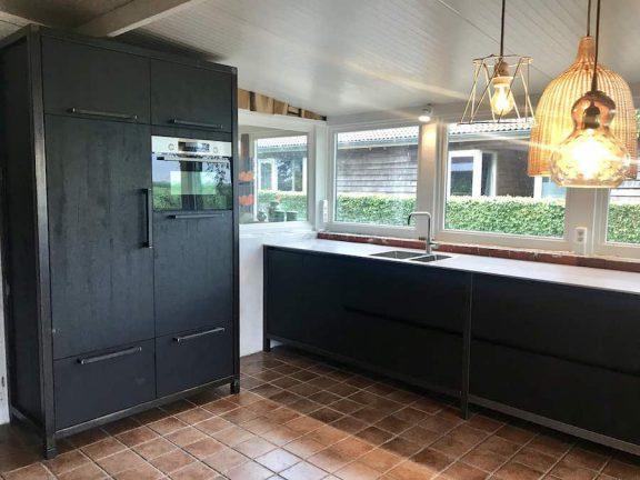 Zwarte Keuken Met Licht Grijs Blad Stalen Poten En Uitzicht Door Grote Ramen.